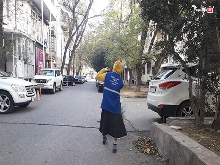 Bakıda qolu sarğılı qadın küçə süpürür – FOTO