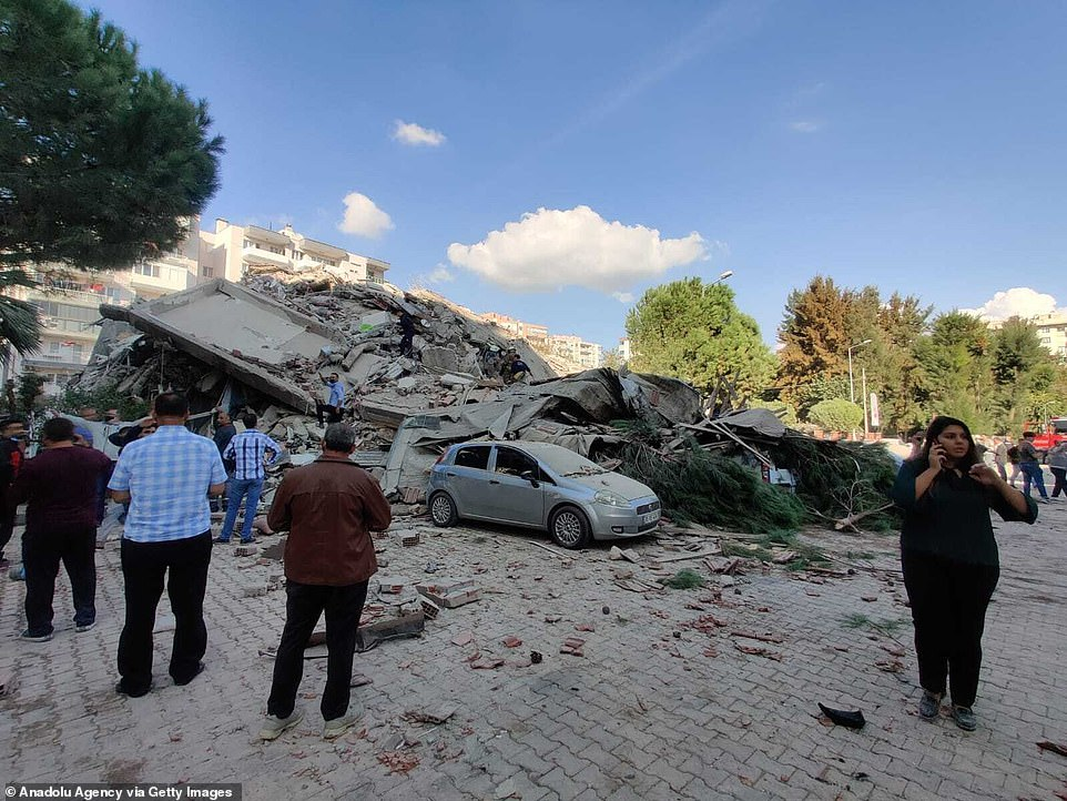 35039320 8897247 people look at the rubble of a building in izmir after the earth a 90 1604062840777